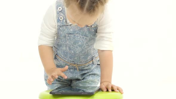 Thumbnail for Child Near a Green Highchair and Holds a Laptop. White Background