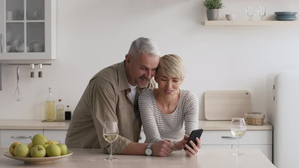 Mature Couple Using Smartphone In Modern Kitchen At Home