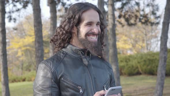 Thumbnail for Adult Middle Eastern Rocker with Long Curly Black Hair Holding Smartphone and Listening To Music in