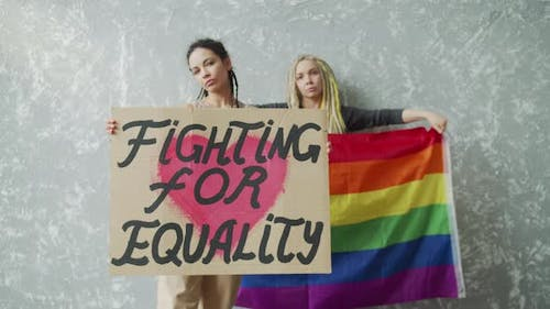 Teenagers are Standing By the Wall with LGBT Poster and Rainbow Flag