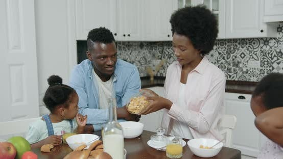 Thumbnail for African American Couple with Small Kids Sitting at Kitchen Table and Have Breakfast