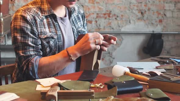 Man in Checked Shirt Sewing Leather Item