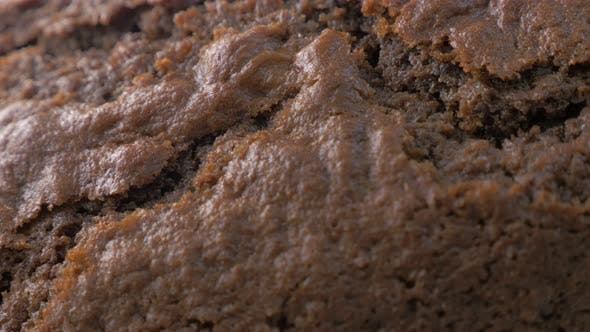 Shiny crackled browny type cake surface close-up panning 4K 3840X2160 UltraHD footage - Tasty lookin