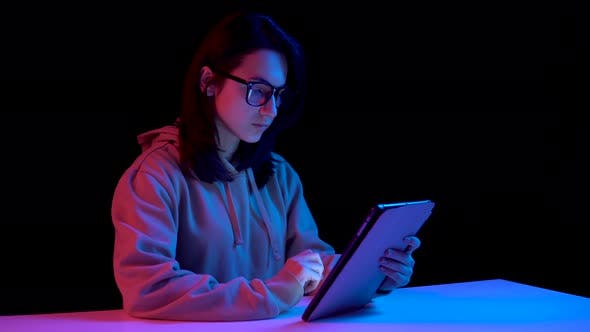 Thumbnail for Young Woman with a Tablet. A Woman Is Using a Tablet. Blue and Red Light Falls on a Woman on a Black