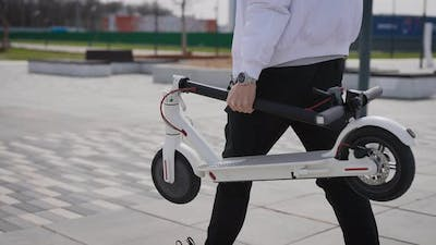 An Unrecognizable Man is Carrying an Electric Scooter