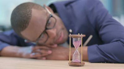 African Businessman Waiting Looking at Hourglass