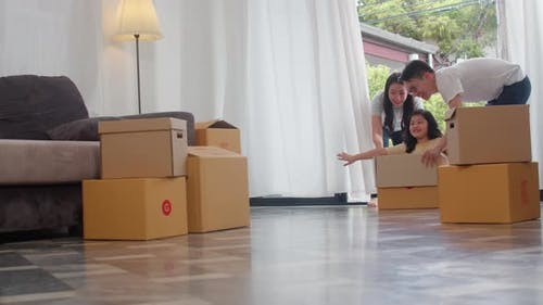 Happy Asian young family having fun laughing moving into new home.