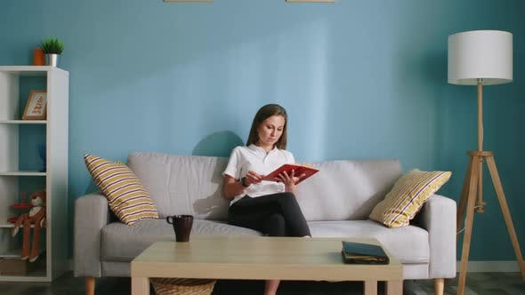 Thumbnail for Woman Is Sitting On Sofa And Reading Book