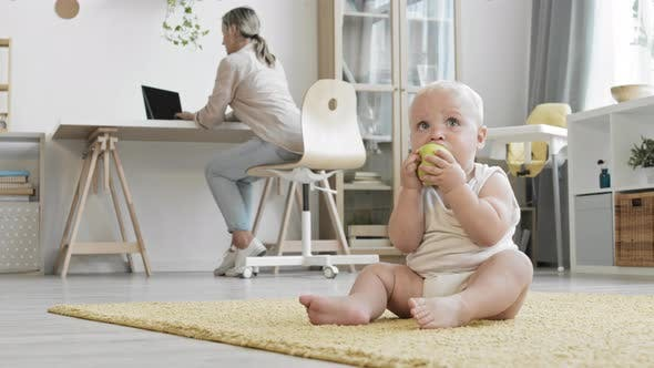 Young Mother Working while Baby Playing