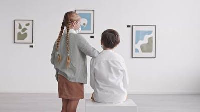 Girl Talking to Boy in Gallery