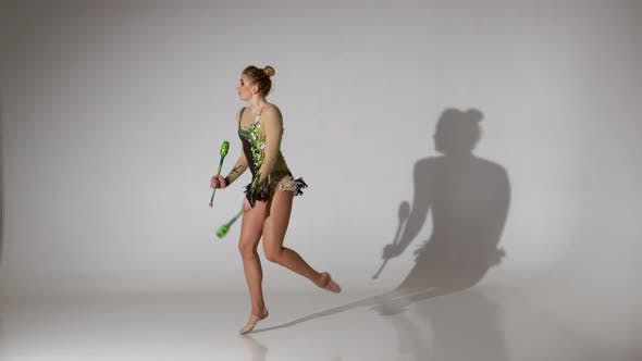 Thumbnail for Rhythmic Gymnast Kneeling and Holding Her Mace It Makes Acrobatic Movements. White Background