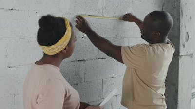 African-American People Measuring Wall and Remodeling Apartment