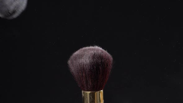 Cover Image for Two Makeup Brushes with Powder on a Dark Background