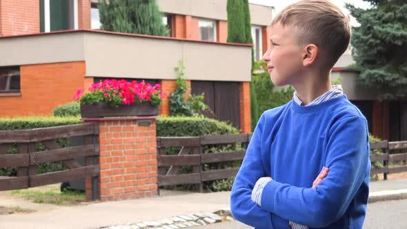 Thumbnail for A Young Boy Looks Around in a Suburban Street