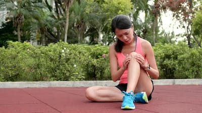 Sport woman getting hurt on legs at outdoor park