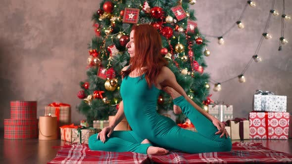 Thumbnail for Slim Woman Practices Yoga Background Christmas Tree. Weight Loss After New Year