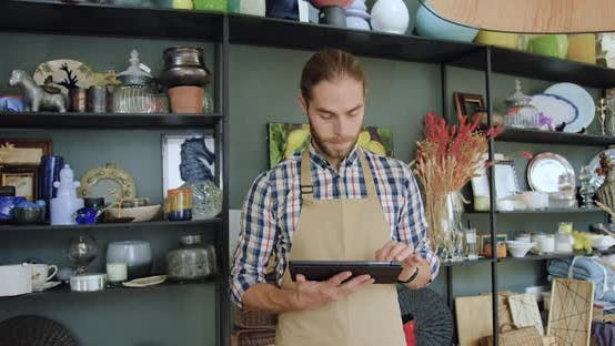 Thumbnail for Bearded Seller in Apron Uses Tablet Device and then Looking at Camera