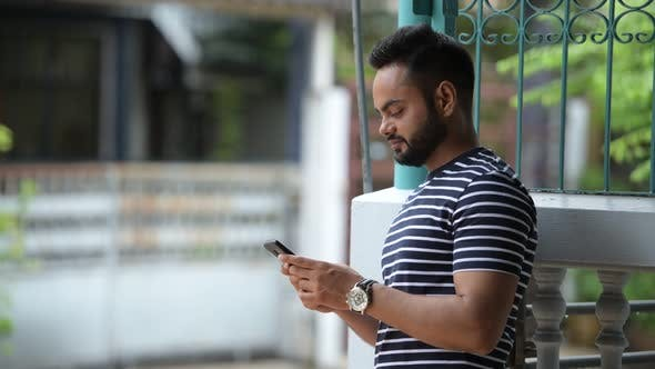 Young Happy Bearded Indian Man Using Phone and Waving Hand Outdoors