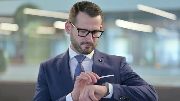 Thumbnail for Portrait of Middle Aged Businessman Waiting and Checking Smartwatch