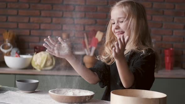 Thumbnail for Young Girl Is Clapping Hands in Flour in a Kitchen