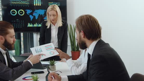 Businesspeople Analyzing Financial Report with Diagramms During Joint Meeting