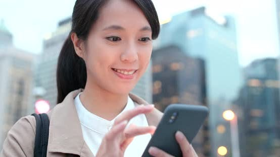 Thumbnail for Young business woman work on mobile phone at night