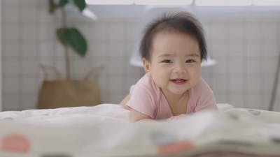 Slow Motion Happy Asian Baby Crawls In The Living Room. Infant Baby Plays with Family.