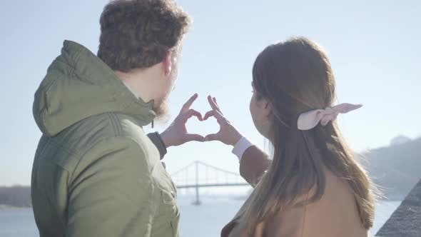 Thumbnail for Close-up of Young Man and Woman Making Heart Shape with Hands. Couple in Love Looking at Each Other