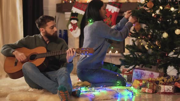 Thumbnail for Man and Woman Sitting Near Christmas Tree in Modern Room. Girl Hanging Toys, Man Playing Guitar