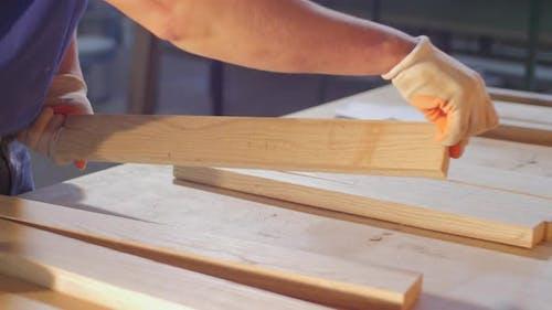 Carpenter arranging wood planks