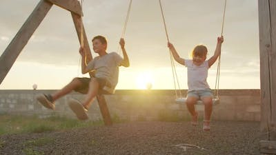 Boy and Girl Ride a Swing at Sunset. Childhood and Friendship Concept.