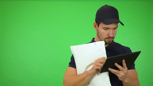 Thumbnail for A Young Handsome Mailman Works on a Tablet, Then Smiles at the Camera - Green Screen Studio