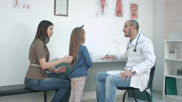 Cover Image for Mother with Girl Being Examined By Male Pediatrician with Stethoscope
