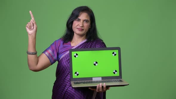 Thumbnail for Mature Beautiful Indian Woman Showing Laptop and Pointing Up