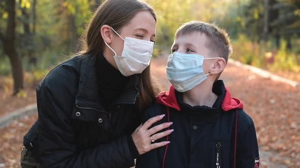 Thumbnail for Happy Woman and Boy Wearing Protective Medical Masks at the Park