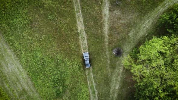 Aerial view of white car driving on country road in forest. Cinematic drone shot flying over gravel