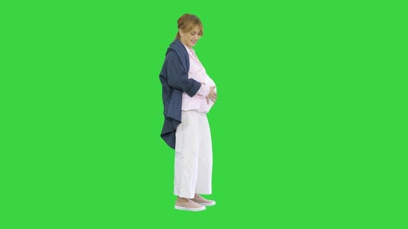 Pregnant Woman Caressing Her Belly on a Green Screen, Chroma Key.