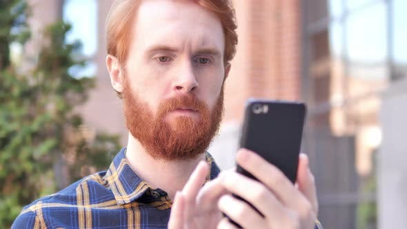 Thumbnail for Man Using Smartphone while Sitting Out