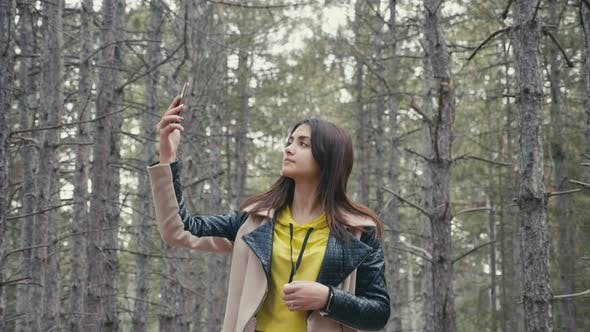 Thumbnail for Pretty Girl Seeking a Signal To Call From Her Smartphone in a Forest in Slo-mo