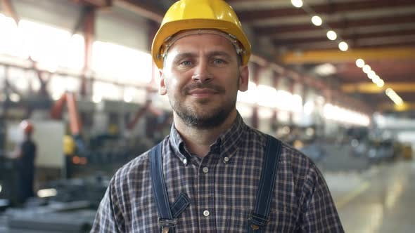 Caucasian Factory Technician Smiling with Satisfaction