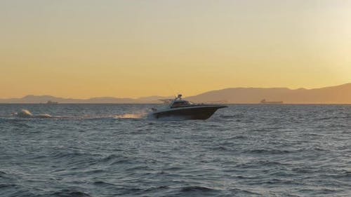 Black and White Private Motor Yacht in the Sea on Sunset