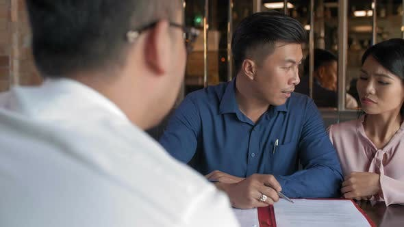 Clients Discussing Contract with Lawyer