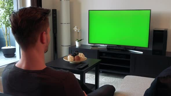 Thumbnail for A Man Watches a TV with a Green Screen in a Cozy Living Room