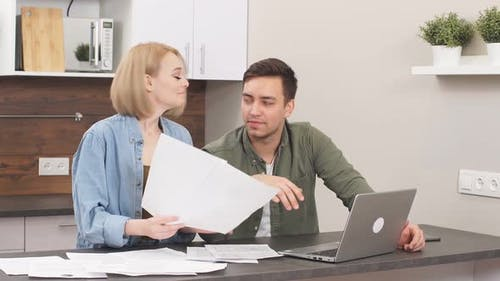 Young Caucasian Spouses Sitting with Laptop and Documents
