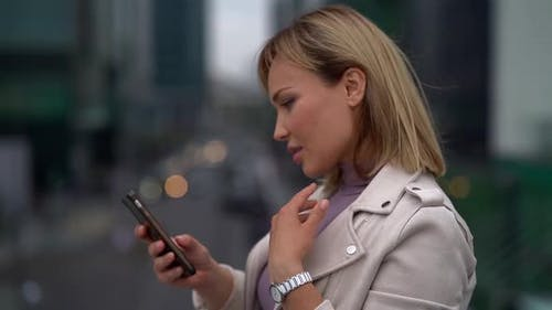 Portrait of a Beautiful Blonde Middle-aged Woman Typing on a Mobile Phone Outdoors in the City.