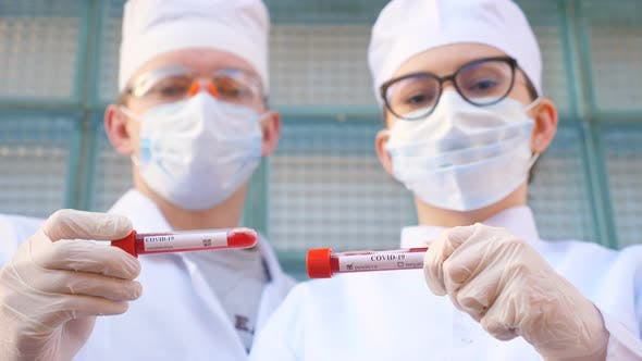 Thumbnail for Male and Female Doctors Holds Test Tube with Blood Sample To Coronavirus. Two Medics with Protective