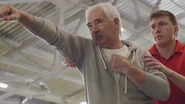 Thumbnail for Trainer Working with Aged Man in Gym
