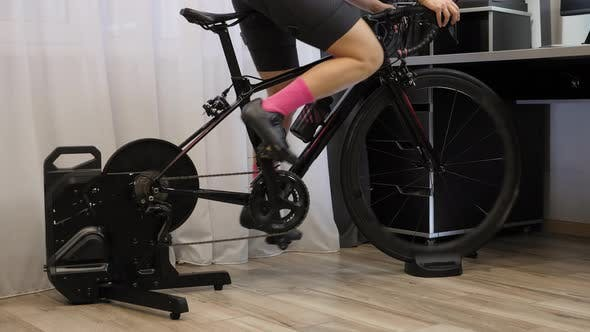Woman is pedaling out of saddle on indoor smart bicycle trainer.