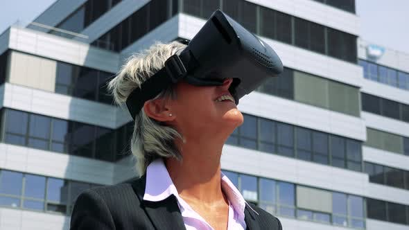 Thumbnail for Business Middle Age Woman Uses Virtual Reality Glasses - Company Building in Background - Closeup
