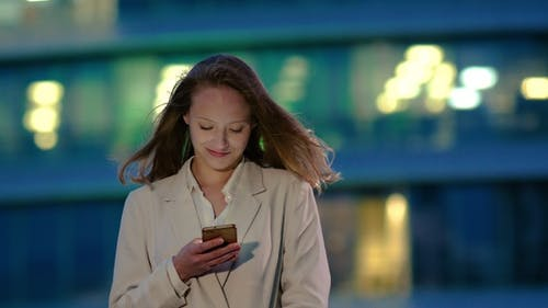 Young girl at night reads message on the smartphone